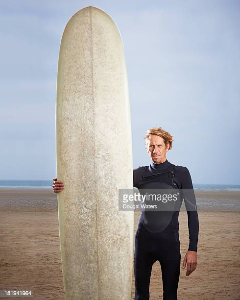 Male surfer standing with long board.