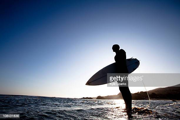 A male surfer stands on a rock while being silhouetted by the setting sun.