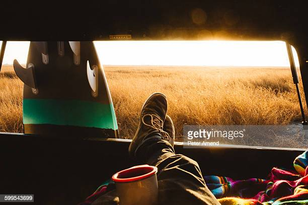 Male surfer with feet up in back of jeep at sunset, San Luis Obispo, California, USA