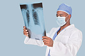 Male surgeon analyzing x-ray report over light blue background