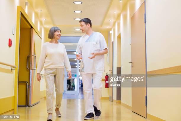Male surgeon and senior woman walking in corridor