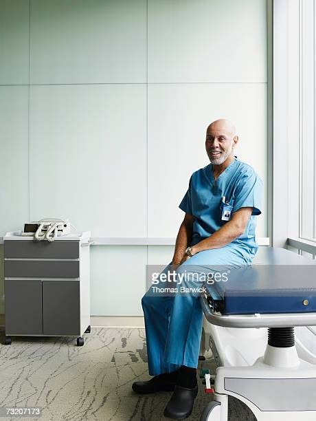 Male surgeon sitting on gurney in hospital corridor, smiling