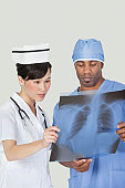 Male surgeon with nurse examining x-ray report over gray background