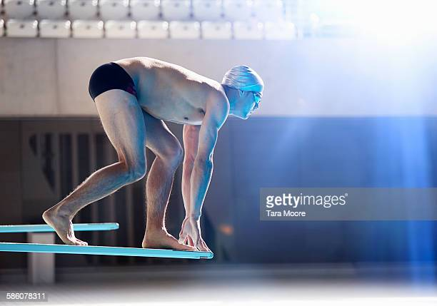 male swimmer about to dive off board