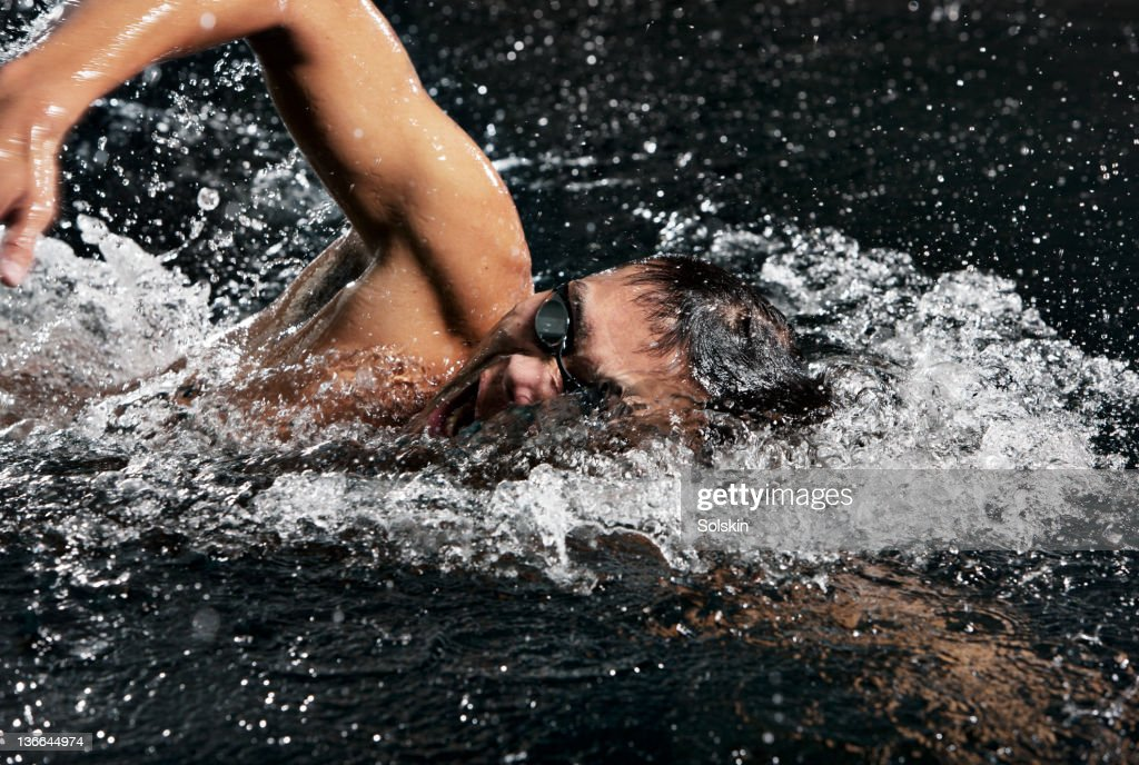 male swimmer doing crawl strokes in pool : Stock Photo