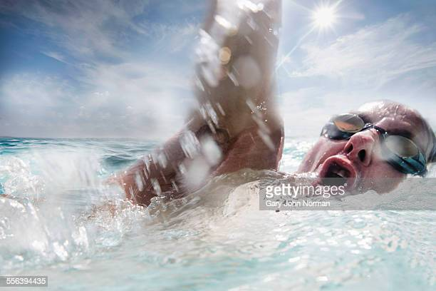 Male swimmer training in open water, close up