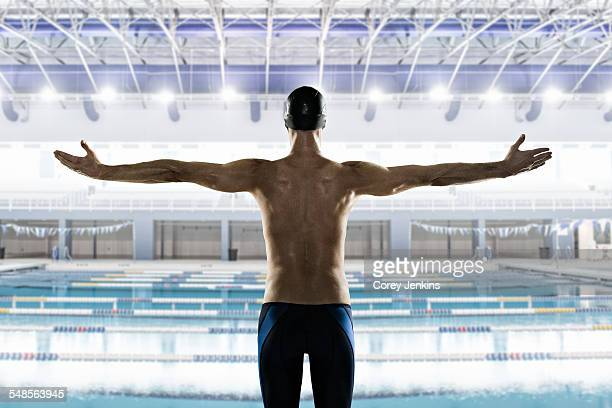 Male swimmer with arms out, rear view