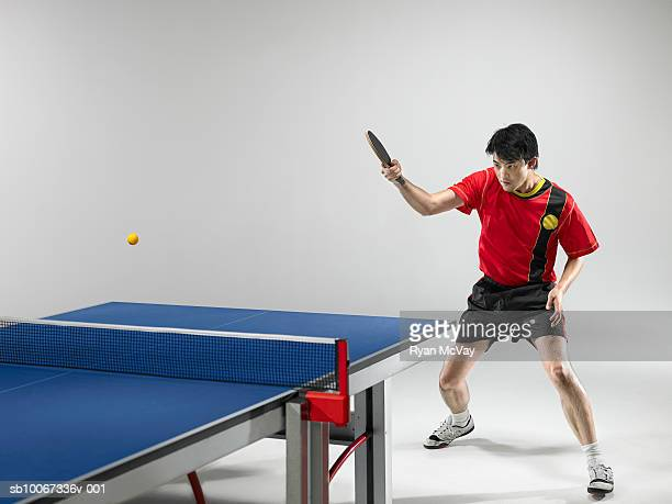 Male table tennis player hitting ball  (studio shot)