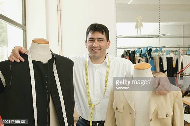 Male tailor standing with arms around mannequins, smiling, portrait