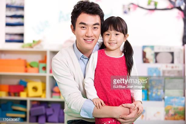 Male teacher and cute little girl