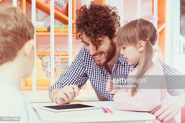 male teacher, cute primary school girl, tablet