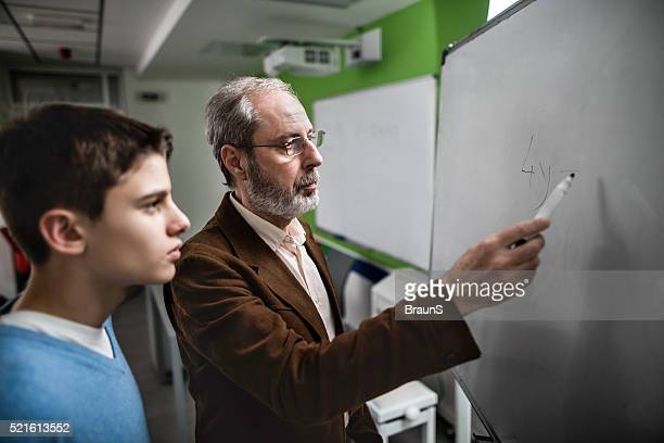 Male teacher explaining a lesson to high school student.
