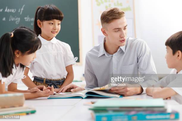 Male teacher helping students study in classroom