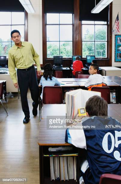 Male teacher looking at a boy playing video game in a classroom