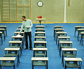 Male teacher setting out papers in empty exam hall