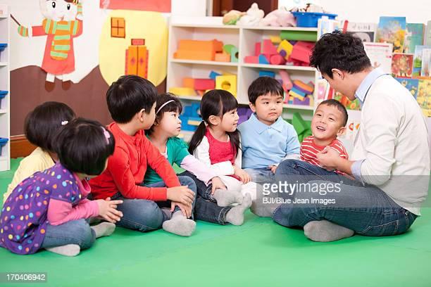 Male teacher sitting on floor with cute kindergarten children