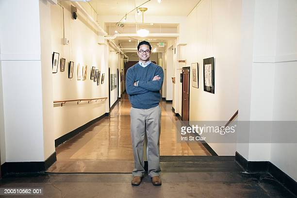 Male teacher standing in school corridor, arms crossed, portrait