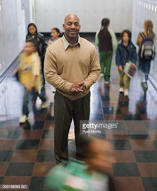 Male teacher standing in school corridor, portrait (blurred motion)
