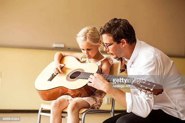 Male teacher teaching girl to play guitar