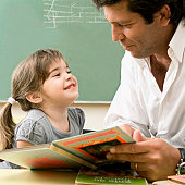 Male teacher teaching his student in a classroom