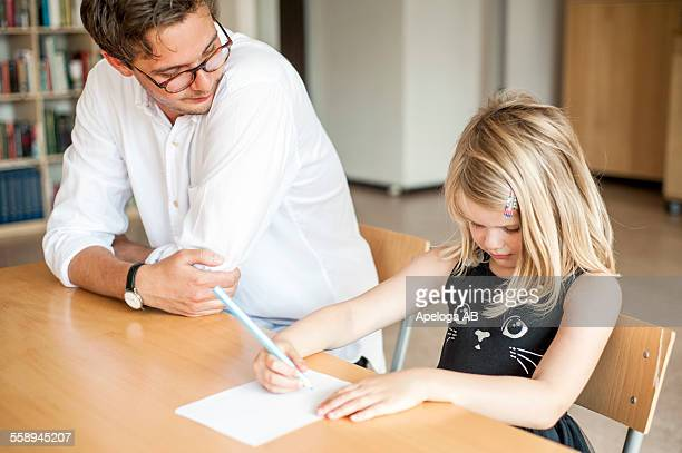 Male teacher watching girl drawing in paper during art class