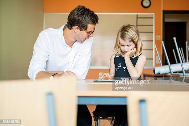 Male teacher watching girl using digital tablet in classroom