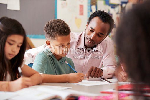 Male teacher working with elementary school boy at his desk : Stock Photo