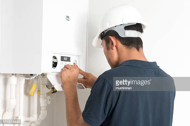 Male technician working in a boiler in a white room