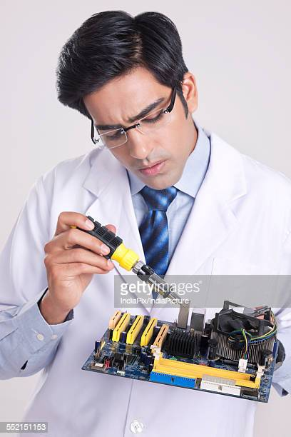 Male technician working on machine part against gray background