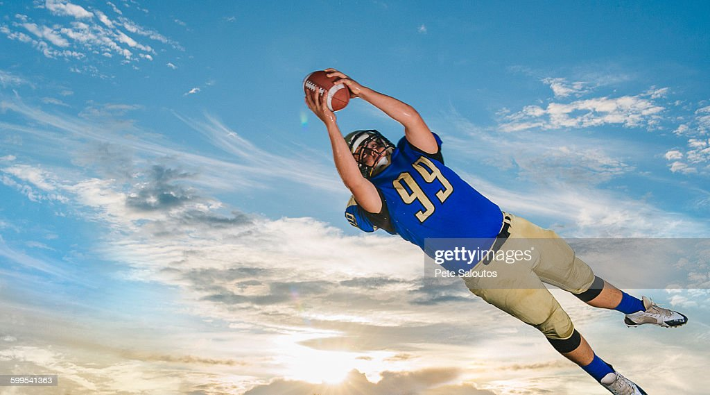 Male teenage American football player catching ball mid air against blue sky