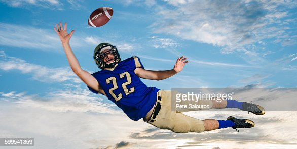 Male teenage American football player reaching to catch ball mid air against blue sky