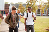 Male Teenage Students Walking Around College Campus Together