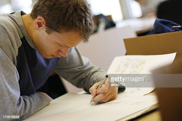 A male teenager drawing on paper