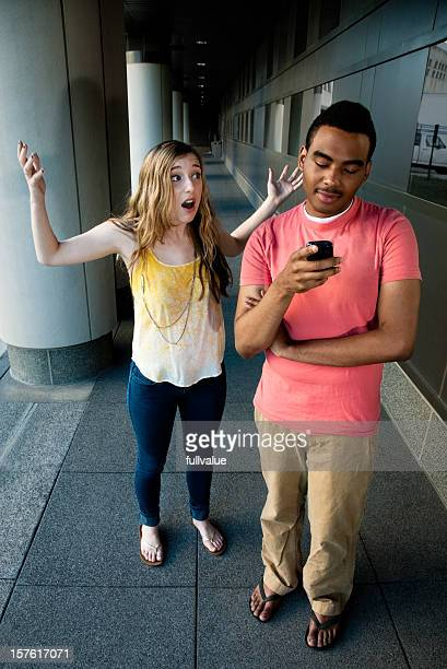 Male teenager ignoring girl while texting