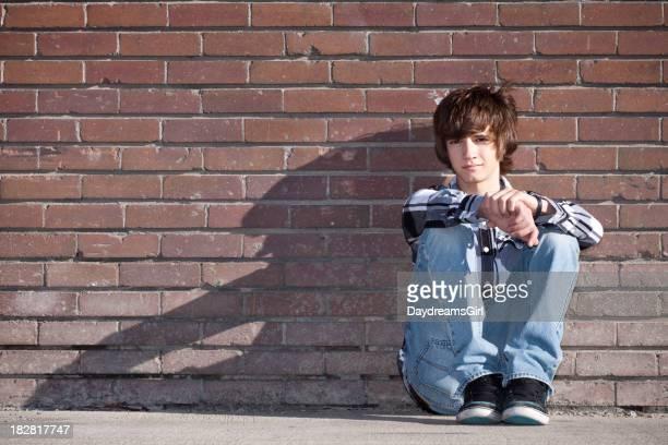 Maschio adolescente seduto da muro di mattoni