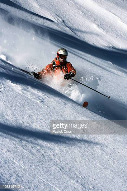 A male telemark skier charging untracked powder on a sunny day in Montana.