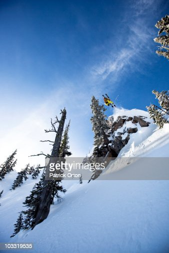 A male telemark skier front flips off a cliff in Montana.