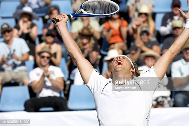 Male tennis player celebrating victory by crowd