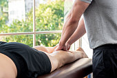 Male therapist giving leg massage to athlete patient on the bed in clinic, sports physical therapy concept