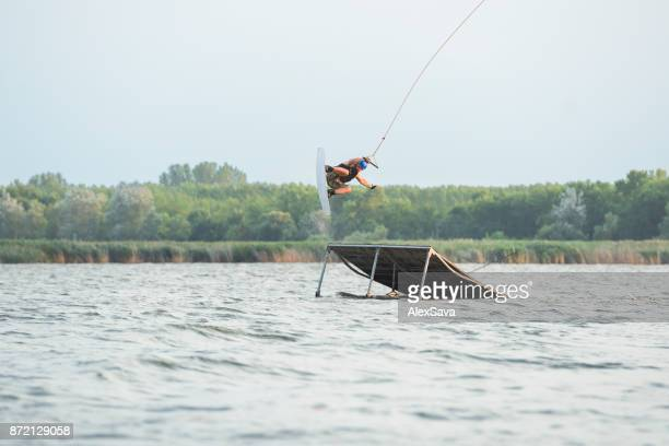 Male thrill-seeker perfroming extreme midair stunts with wakeboard