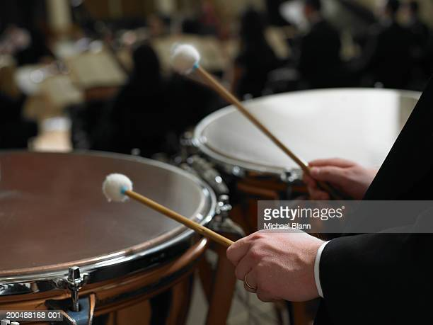 Male timpanist playing kettledrums in orchestra, close-up