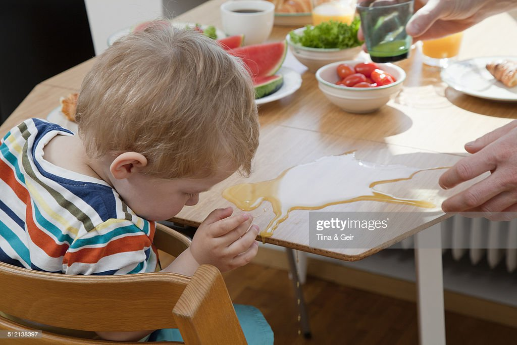 Male toddler accidently spilling orange juice at breakfast table