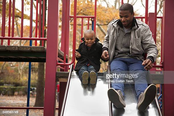 Male toddler and father side by side on park slide