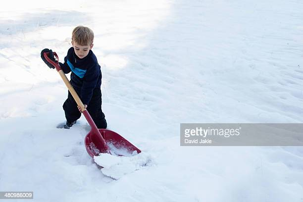 Male toddler digging snow with large shovel