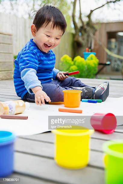 Male toddler drawing in garden
