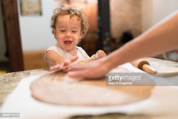 Male toddler helps his mom make homemade pizza.