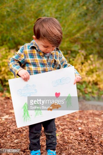Male toddler holding crayon drawing : Stock Photo