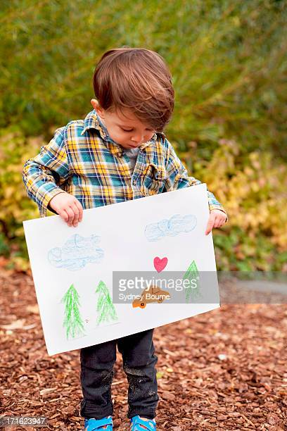 Male toddler holding crayon drawing