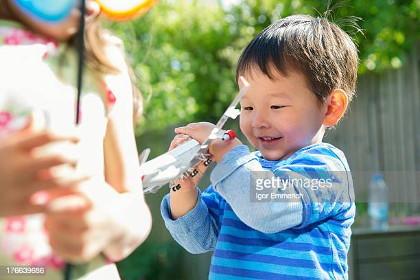 Male toddler in garden with toy airplane