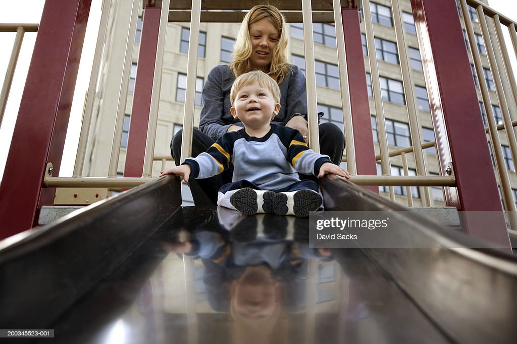 Male toddler (15-18 months) on slide, mother in back, low angle view : Stock Photo
